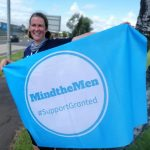 Photo of Christine Maxwell holding a light blue flag with a white circle that reads: MindTheMen #SupportGranted